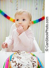 Eat smeared baby eating birthday cake