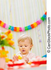 Eat smeared baby eating orange at birthday party