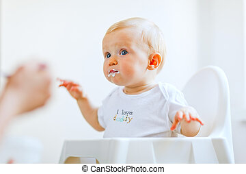Eat smeared lovely baby in baby chair feeding by mother -...