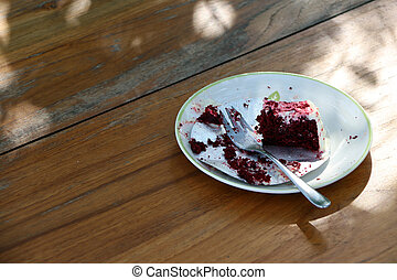 Eaten cake in the white plate with small spoon on the wooden table. an item of soft, sweet food made from a mixture of flour, shortening, eggs, sugar, and other ingredients, baked and often decorated.