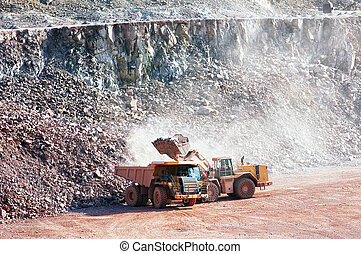 eath mover loading stones on a dumper truck. mining...
