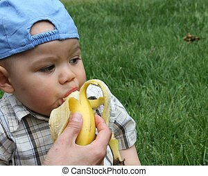Eating a Banana - Baby taking a bite out of a banana