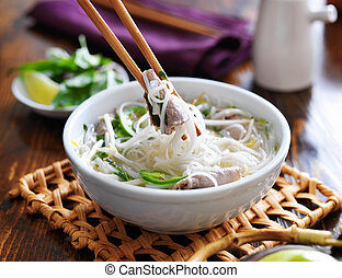eating a bowl of pho with noodles and beef
