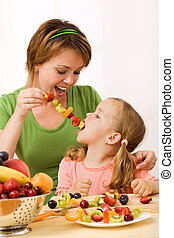 Eating a healthy snack - fruit slices on stick