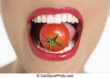 Eating a red tomato macro of woman mouth