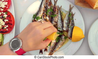 Eating appetizing sardines dish served with parsley and...