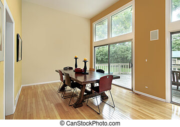 Eating area with two story windows and orange wall