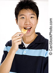 Eating Chips - A young asian man eating potato chips