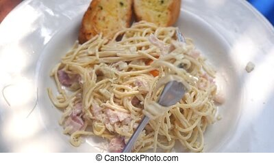 Eating close up of Italian pasta carbonara with parmesan,...