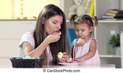 Eating Eggs - Young mother sharing a boiled egg with her...