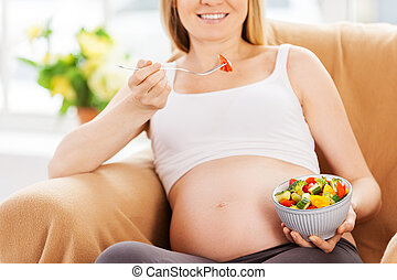 Eating fresh salad. Cropped image of happy pregnant woman sitting on the chair and eating salad