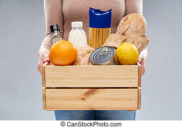 close up of woman with food in wooden box