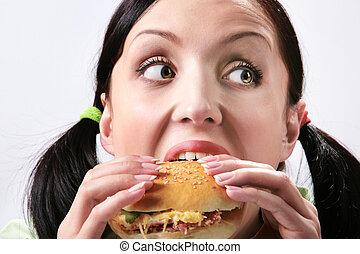 Eating hamburger - Image of hungry girl eating hamburger and...