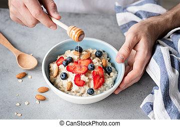 Eating healthy breakfast oatmeal porridge with fresh berries and nuts