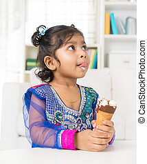Eating ice cream. - Little Indian girl licking her lips with...