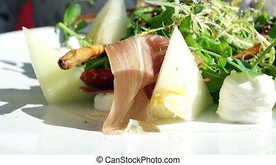 Eating lettuce, melon and ham salad at the restaurant, haute cuisine. 4K close-up video