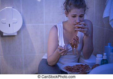 Eating out of control - Image of depressed girl eating out...