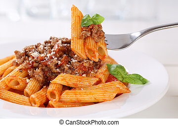 Eating Penne Rigate Bolognese or Bolognaise sauce noodles pasta meal on a plate
