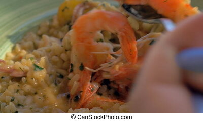Eating risotto with squid and prawns in sea food restaurant...