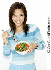 Eating Salad - A pretty young asian woman with a small bowl...