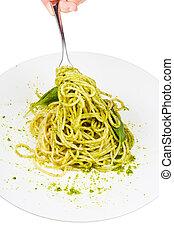 eating spaghetti with pesto isolated on white background