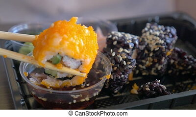 Eating sushi rolls with soy sauce