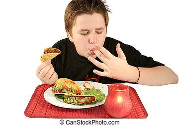 eating tacos - boy licks his fingers while enjoying his taco...