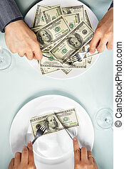 People hand eating the dollar bills on the plate