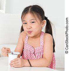 Asian kid eating yoghurt - Eating yogurt. Happy Asian kid...