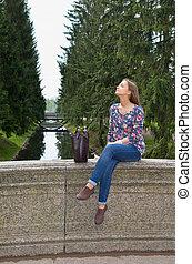 eautiful girl sits on an old stone bridge