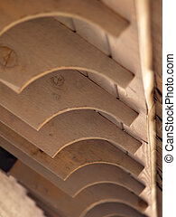 Closeup detail of the wooden beams of a park shelter over a picnic area. A decorative quarter-round has been cut into the end of each board.