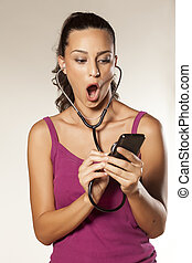 eavesdrop - young beautiful shocked girl uses a stethoscope...