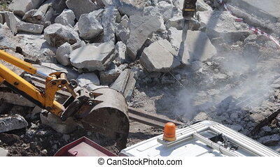 eavy machines working in teamwork to clean broken concrete by digging and drilling