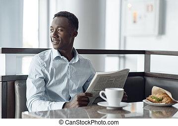 Ebony businessman having lunch in office cafe