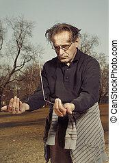 Eccentric spiritual man training dowsing in city park - Man...
