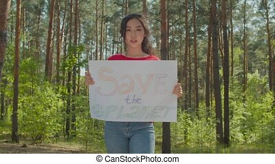 Charming environmental friendly young asian woman in casual clothes holding broadsheet placard, protesting against environmental pollution and plastic problems, chanting save the planet in forest.