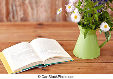 book and flowers in jug on wooden table