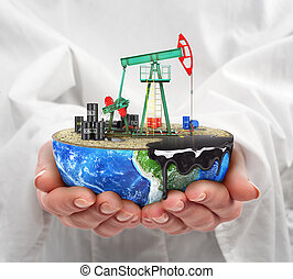 Eco-concept. A cut planet with oil pumpjack in woman's hands isolated on a white background. The concept of natural resource extraction.