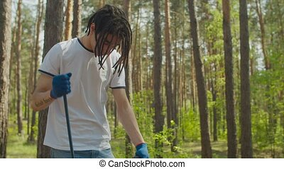 Eco-friendly stylish young arabic male volunteer caring for purity of nature and preserving ecology, cleaning up plastic waste and garbage in forest using garden tool. Environmental pollution.
