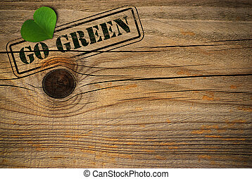wooden background with green natural heart and go grren message