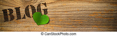 wooden background with the word blog and green heart