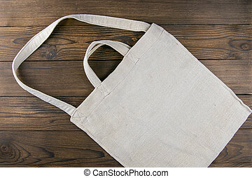Eco friendly canvas shopping white bag on the dark wooden table background. Top views with clear space