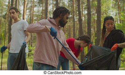 Eco-friendly people cleaning woodland from trash - Group of ...