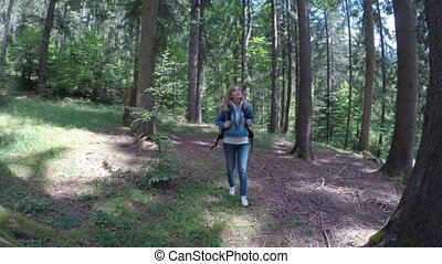 Eco friendly young woman walking alone in forest admiring...