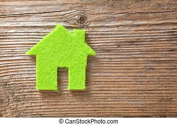 Eco house concept - Green small house on wooden background