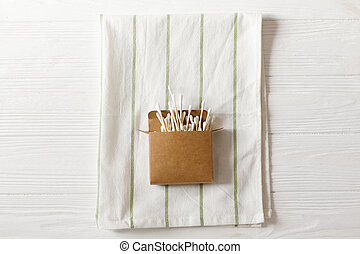 eco natural bamboo ear sticks flat lay on towel, rustic background. sustainable lifestyle concept. zero waste, plastic free items. stop plastic pollution. reuse, reduce, recycle, refuse
