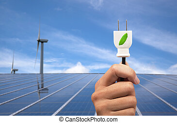 eco power concept. hand holding green power plug and solar panel and wind turbine background