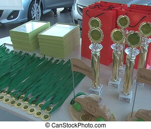 Eco rally medals and cups prepared for winners. Artificial...