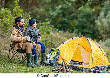 eco tourism - happy father and son sitting in camping with...