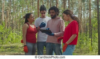 Eco volunteers planning forest cleanup from trash - Positive...
